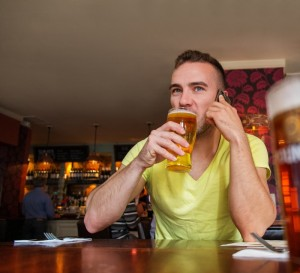 Canstock Man in Bar on phone while drinking